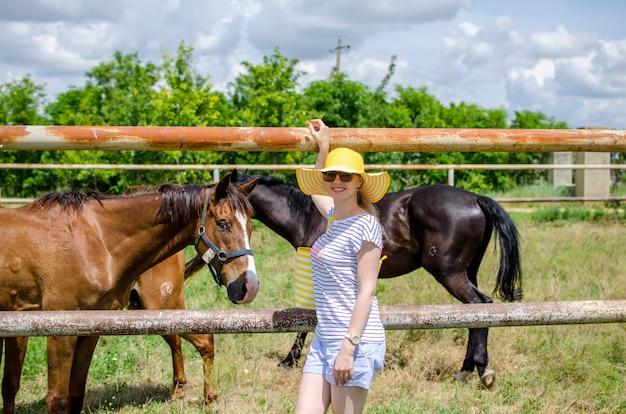 馬とパドックの近くに立って、笑みを浮かべて、カメラを見て、黄色い帽子と夏服の白人少女。動物とスタッドファームへの遠足。コピー空間