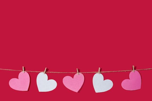 赤の古典的な背景にピンクと白のハートのガーランド。自然なロープと洗濯はさみ。愛、結婚式、ロマンチックな関係、バレンタインデーの宣言の概念。コピースペース