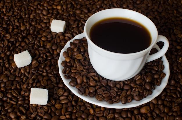 Белая чашка черного кофе на кофейных зернах