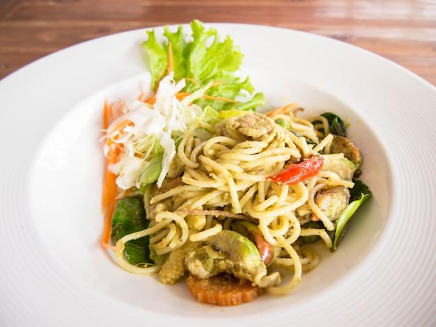 すぐに食べられる白い皿にスパゲッティとグリーンカレーソースを茶色の木製テーブルに置いたもの。