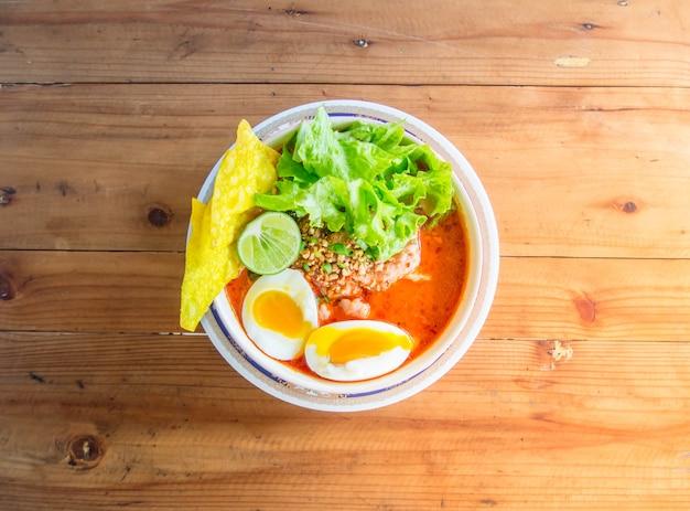 豚肉麺トムヤム、木製のテーブルの上にカップに凝縮水卵。