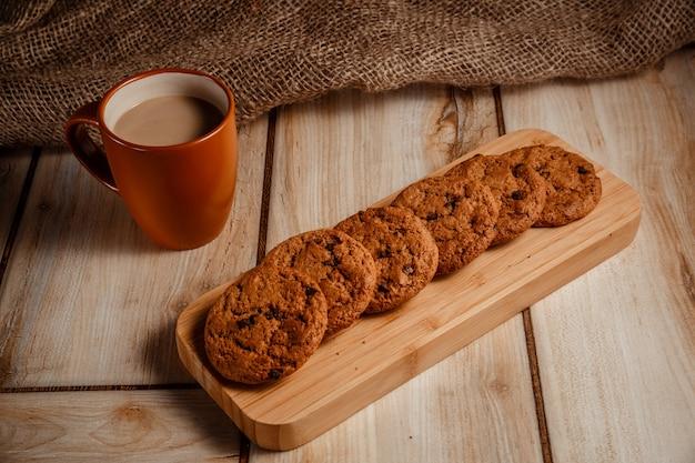 Овсяное печенье на деревянной подставке и кофе с молоком