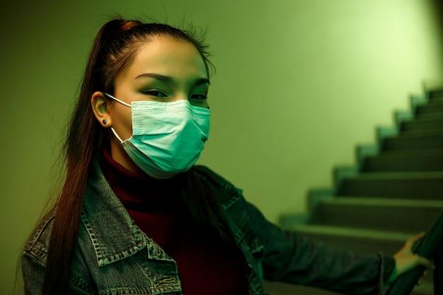 ぼやけた階段と防護使い捨て医療マスクの若い女性