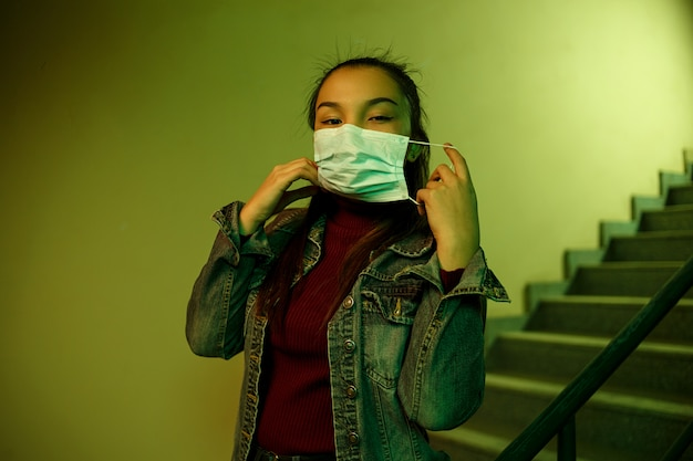 階段と防護使い捨て医療マスクの若い女性