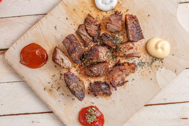 Кусочки жареного мяса со специями на деревянном подносе с четырьмя видами соусов к мясу