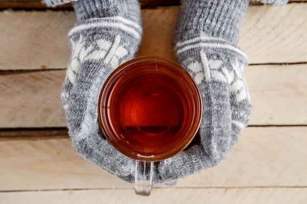 お茶のガラスを保持している暖かい手袋で女性の手
