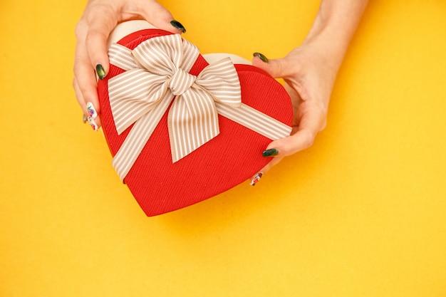 Картонная биоразлагаемая подарочная коробка в форме сердца в женских руках