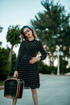 Молодая женщина в винтажном черном платье в горошек с ретро чемоданом в руке позирует на улице