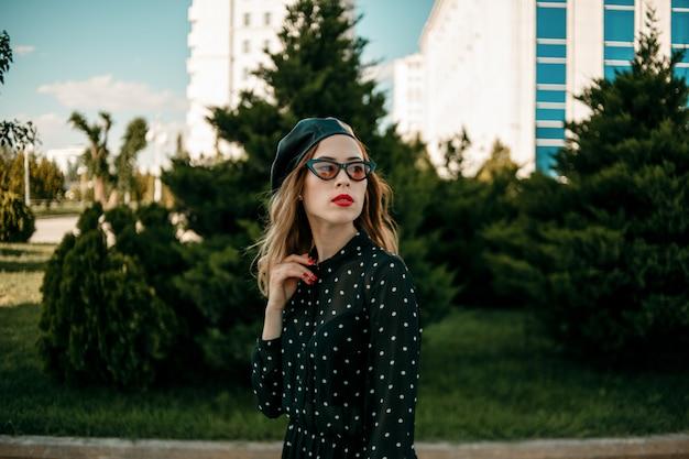 外でポーズヴィンテージ黒水玉ドレスの若い女性