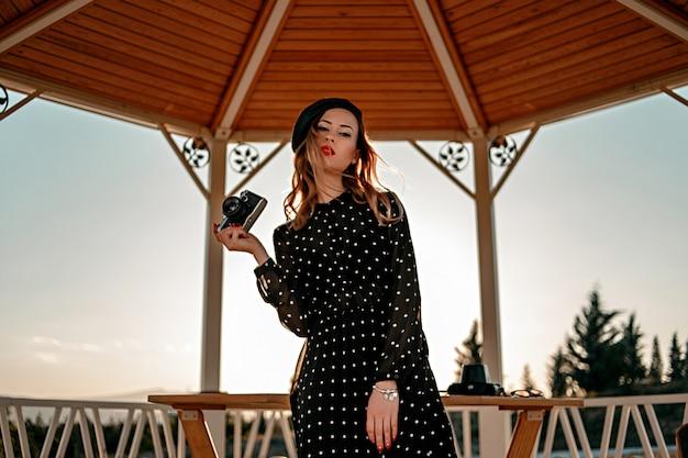 Молодая женщина в винтажном черном платье в горошек со старой камерой в руках позирует на улице