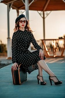 レトロなスーツケースを手に外でポーズヴィンテージ黒水玉ドレスの若い女性