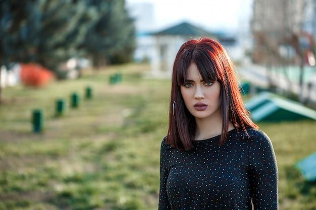日没時にポーズを外の黒のドレスで重いと不機嫌そうな表情で美しい少女