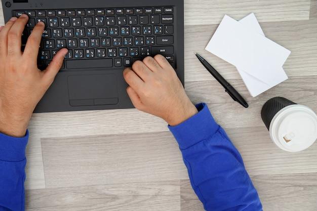 ノートパソコンで入力する若い男の手。上からの眺め