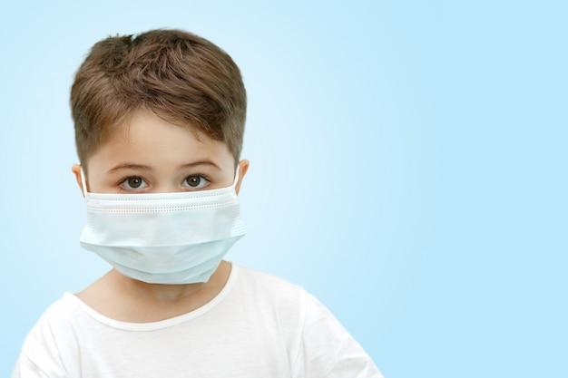 孤立した背景に医療マスクで白人少年