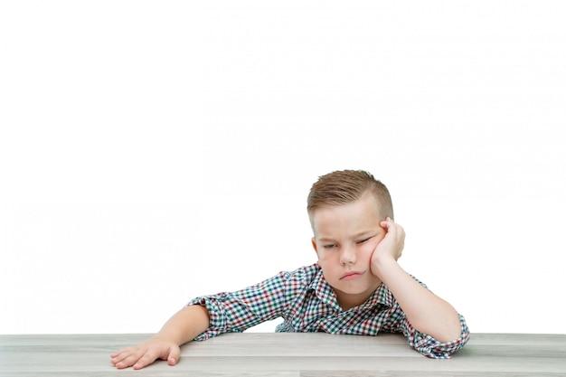格子縞のシャツを着た白人の学齢期の少年はテーブルに座って眠りに落ちる