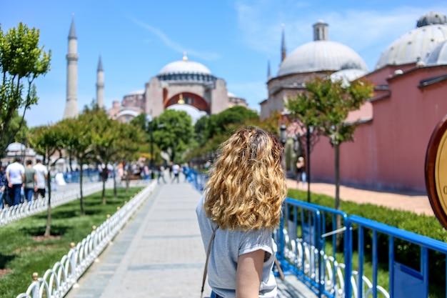 若い女の子がアヤソフィアに向かって歩きます。背面図。七面鳥。イスタンブール