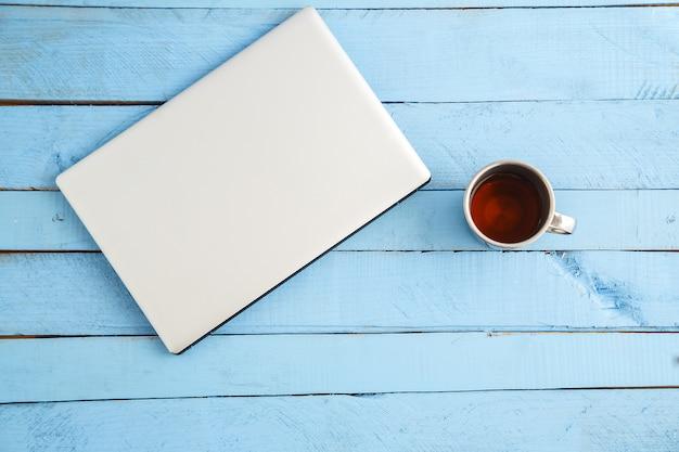 灰色のラップトップと青い木の飲み物のカップ