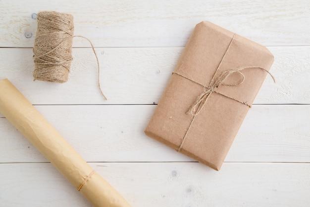 小包、ギフト環境に優しい紙で梱包され、明るい木製の背景に梱包するためのより糸。上からの眺め