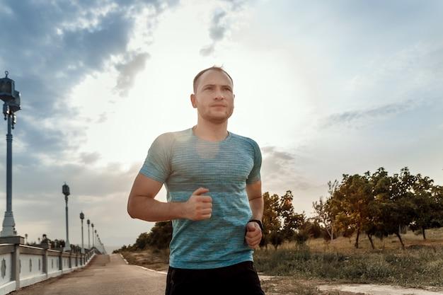 Портрет кавказского парня в синей футболке и черных шортах, который тренируется и бежит по асфальтовой дорожке во время заката
