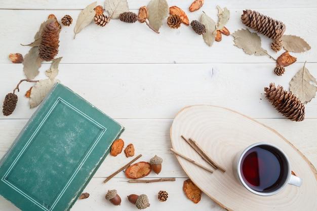 ビンテージの本と木製の背景にレトロなマグカップでドリンク。上面図
