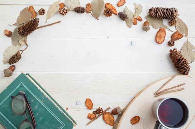 Винтажная книга и питье в ретро кружке на деревянной предпосылке. вид сверху