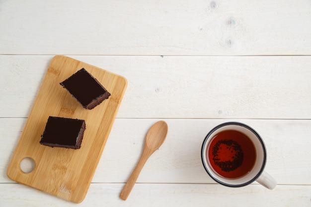 テキスト用のスペースと白い木製の背景にお茶のカップと竹皿にブラウニーケーキ