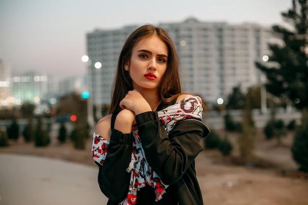 Молодая красивая девушка в черном пиджаке с шарфом позирует вечером на улице.