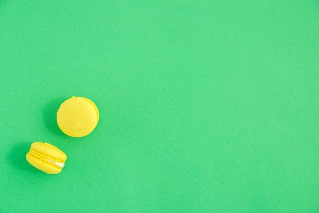 緑の背景にカラフルなマカロンまたはマカロンクッキー