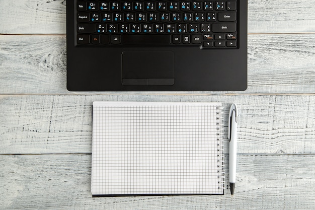ホワイトペーパーのメモ帳とビンテージのぼろぼろの白い木の上のノートパソコン、トップビュー