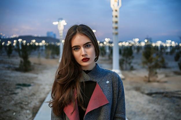 Портрет молодой красивой брюнетки в сером пальто на фоне заката и ночных огней