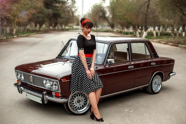 Портрет кавказских красивая молодая девушка в черном винтажном платье, позирует возле старинных автомобилей
