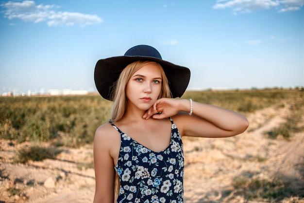 黒い帽子と花柄のドレスを着た青い瞳の金髪女性のクローズアップの肖像画。彼女は日没時にブドウ園でポーズをとっています。