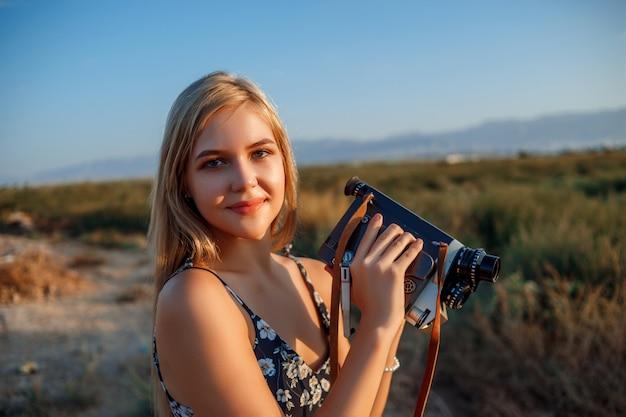 日没時にブドウ畑でビンテージビデオカメラと花柄のドレスで金髪の女性の肖像画