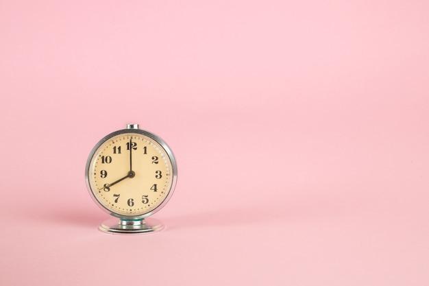 ピンクの孤立した背景に小さなビンテージレトロな目覚まし時計
