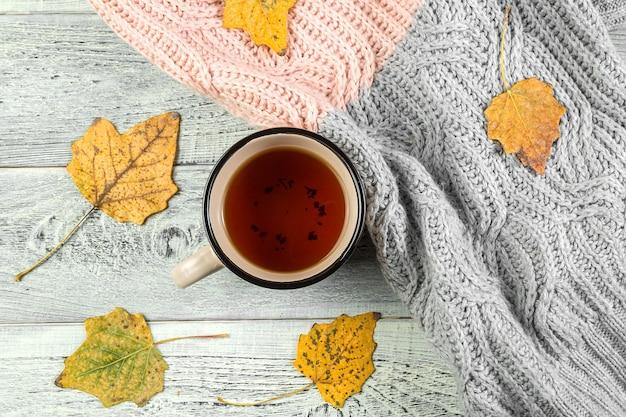黄色の紅葉、古い木製の背景にお茶