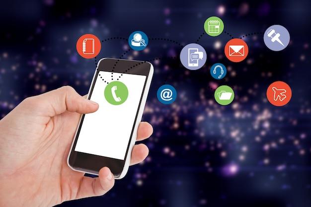 カラフルなアプリのアイコンとスマートフォンを持っている手のクローズアップ