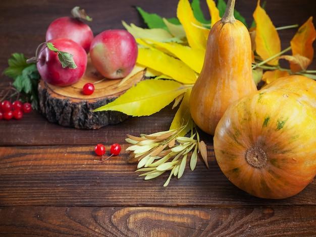 秋の感謝祭のカボチャ、リンゴ、黄色の葉、ガマズミ属の木の果実、木製のテクスチャ背景