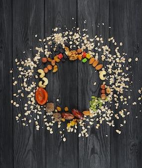 Гранола овсяная, разбросанная по кругу, сухофрукты, орехи, изюм, семечки, на деревянной фактурной пище