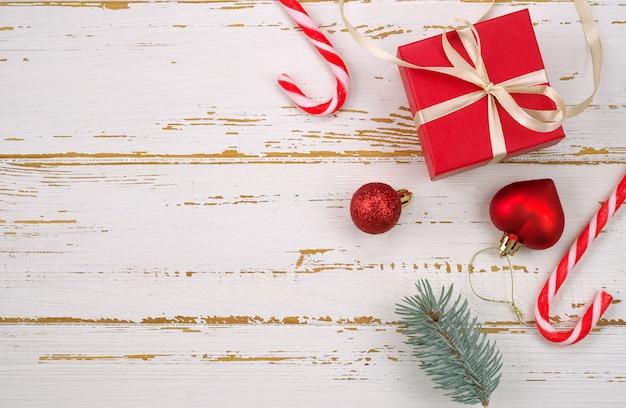 Красная подарочная коробка с елочной игрушкой в форме сердца, еловые ветки, рождественские конфеты, гирлянда на деревянном фоне