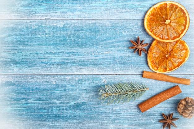 Новогодний фон: сушеные апельсины, анисовые звезды, палочки корицы, веточка ели, на синем деревянном фоне