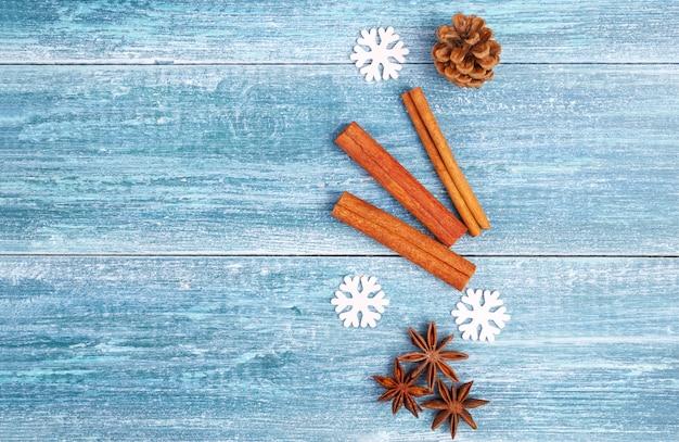 Новогодний фон: анисовые звезды, палочки корицы, веточка ели, на синем деревянном фоне