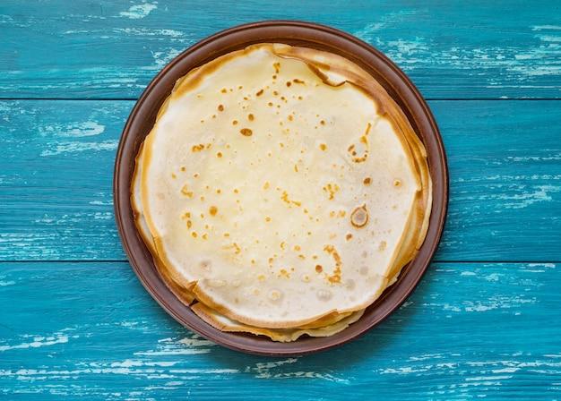 紺碧のテーブルの上の粘土板にロシアのパンケーキ。トップビュー