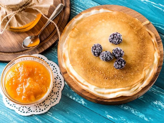 冷凍ブラックベリー、アプリコットジャム、蜂蜜と紺碧のテーブルの上の木の板にロシアのパンケーキ