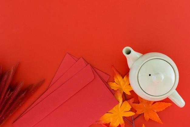 Вид сверху аксессуары чайный горшок и красный конверт для китайского нового года.