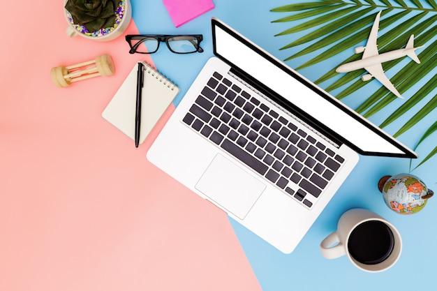空白のラップトップ、クリップボード、トップビューのラップトップの背景とコピースペースピンクとブルーの背景を持つフラットレイアウトオフィスワークスペース