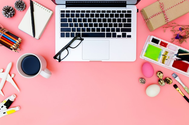 現代の職場のノートパソコンと卵、トップビューのノートパソコンの背景とピンクの背景のイースターの準備をしてペイントセットのフラットレイアウト写真