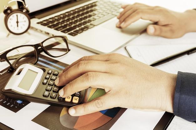 ビジネス会計計画コンセプト、ビジネスを行うための電卓を持つデスクトップのラップトップコンピューターに取り組んで、