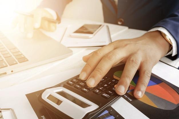 ビジネスを行うための電卓とデスクトップのラップトップコンピューターで作業する