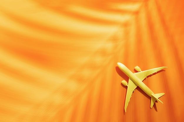 Модель самолета, самолет на оранжевом с копией пространства и тропический пальмовый лист