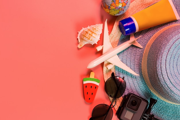 Вид сверху аксессуаров путешественника, тропических пальмовых листьев и самолета на розовый